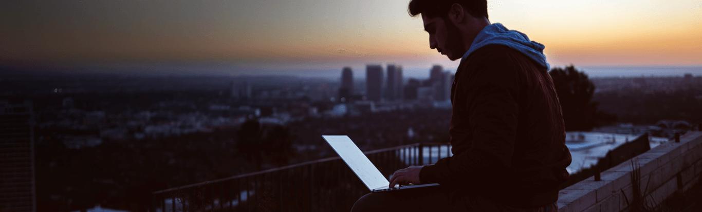 man updating through laptop